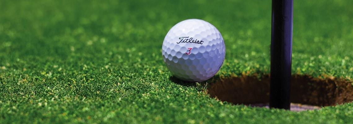 Titleist Golfball liegt vor dem Loch auf dem Putting Green